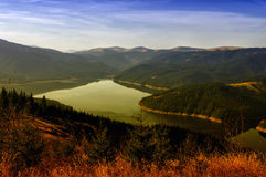 Colors of autumn in a landscape on the mountains. Vidra lake, at sunset - landmark attraction in Romania. Autumn background Royalty Free Stock Image