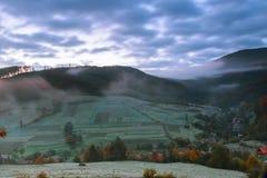 Autumn Landscape Villaggio sul pendio di collina foresta in nebbia sulle montagne alla luce di luna piena di notte Fotografia Stock