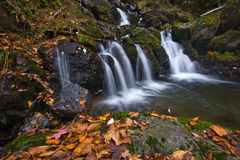 Autumn landscape with a waterfall on the creek taiga. Stock Image