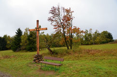 Autumn Landscape with a wooden cross and a bench Royalty Free Stock Photos