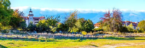 Autumn landscape with wooden fence, trees, houses and mountains Stock Photo