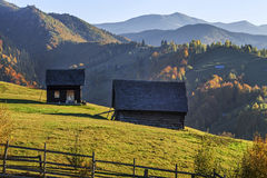 Autumn Landscape with wooden houses on the mountains in afternoon. Stock Image