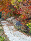 Autumn Lane. Gravel road with fence and gate lined with hay bales and fall foliage Royalty Free Stock Image