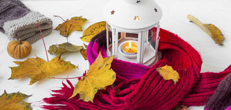Autumn lantern decoration with woolen scarf, dried leaves, pumpk Stock Images