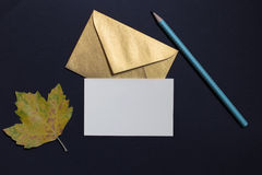 Autumn leaf on black background with card invitation and golden Royalty Free Stock Images