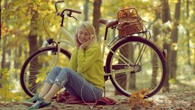 Autumn and leaf fall Dreams. Headphones concept. Carefree woman. Outdoor atmospheric fashion photo of young beautiful