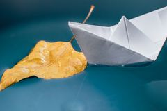 Autumn leaf and a paper boat on the water surface Stock Photography