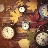 Autumn leafs and alarm clock on table. Royalty Free Stock Photos
