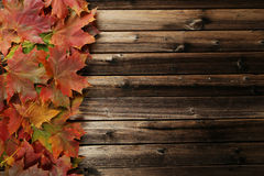 Autumn leafs frame on brown wooden background. Royalty Free Stock Photos