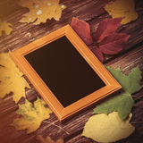 Autumn leafs and frame for photo on  table. Royalty Free Stock Photography