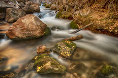 Autumn Leafs on Rocks and Water HDR. Autumn colors on a slow exposure waterfall-river in the Wasatch mountains of Utah USA Stock Photography