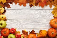 Autumn leaves, apples and pumpkins over wooden background Royalty Free Stock Photo