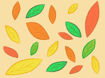 Autumn leaves background. Yellow, red and green autumn leaves on a beige background Royalty Free Stock Photo
