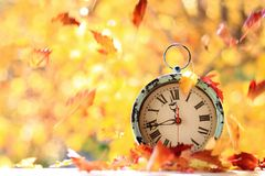 Autumn leaves blowing in the wind across a clock Royalty Free Stock Images