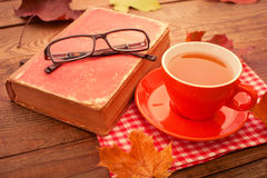 Autumn leaves, book and cup of tea on wooden table Stock Images