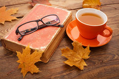 Autumn leaves, book and cup of tea on wooden table royalty free stock images