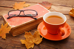 Autumn leaves, book and cup of tea on wooden table Royalty Free Stock Photography
