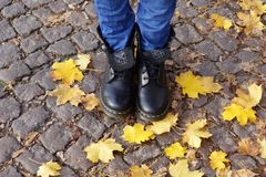 Autumn, leaves, boots, girl, jeans, stone, road, nature, season, season, cold. Autumn, the girl is standing on a wet road in black shoes stock photos