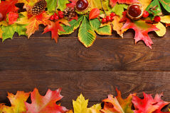Autumn leaves border on wooden background Royalty Free Stock Images