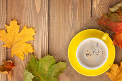 Autumn leaves and coffee cup over wood background Royalty Free Stock Image