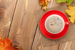 Autumn leaves and coffee cup over wood background Royalty Free Stock Photo
