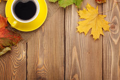 Autumn leaves and coffee cup over wood background Royalty Free Stock Images