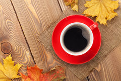 Autumn leaves and coffee cup over wood background Stock Photo