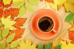Autumn leaves and coffee cup on wood background. Stock Photos