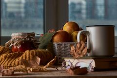 Autumn leaves, cup of coffee, warm scarf, fruits basket and book royalty free stock photo