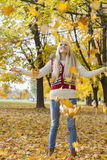 Autumn leaves falling on young woman with arms outstretched in park stock photos