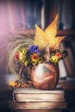 Autumn leaves and flowers home decoration in cup on stack of books Royalty Free Stock Images