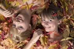 Autumn leaves girls. Portrait of two beautiful young girls in autumn leaves royalty free stock photography