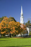 Autumn leaves on green common in front of Presbyterian Church in historical Lexington Massachusetts, New England Royalty Free Stock Image