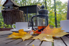 Autumn leaves and a hot cup of steaming tea. Wooden table against Sunny cold day on a natural background. Stock Photo