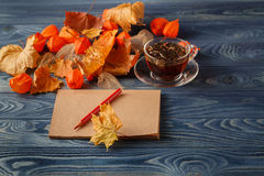 Autumn leaves, hot steaming cup of coffee and on wooden table ba Stock Photo