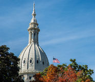 Autumn leaves and the Michigan State Capitol Building. An American flag flies at the historic State Capitol Building in Lansing Michigan stock photos