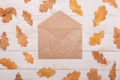 Autumn leaves, notebook and pencils on a white wooden background. Autumn leaves and envelope on a white wooden background. Flat lay, top view, copy space royalty free stock photography