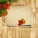 Autumn leaves over wooden background with postcard Stock Photo