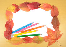 Autumn leaves pencils and sheet of paper Royalty Free Stock Photos
