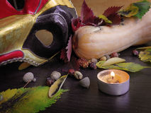 Autumn leaves, pumpkin and a mask with a candle Stock Images