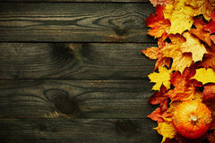 Autumn leaves and pumpkin over old wooden background Stock Photography
