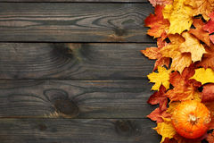 Autumn leaves and pumpkin over old wooden background Royalty Free Stock Photo