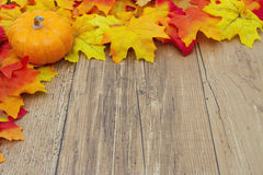 Autumn Leaves and Pumpkin on a Weather Wood Background Royalty Free Stock Photos