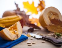 Autumn leaves and pumpkin on a wooden board with a knife Royalty Free Stock Images