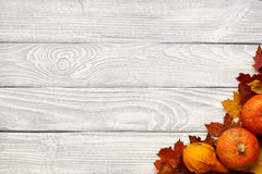 Autumn leaves and pumpkins over old wooden background Royalty Free Stock Photography