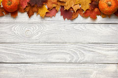 Autumn leaves and pumpkins over old wooden background Royalty Free Stock Image