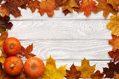 Autumn leaves and pumpkins over old wooden background Stock Images