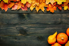 Autumn leaves and pumpkins over old wooden background Stock Photography