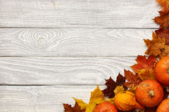 Autumn leaves and pumpkins over old wooden background Royalty Free Stock Images