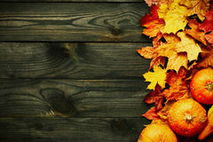 Autumn leaves and pumpkins over old wooden background Stock Image
